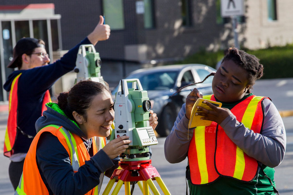 group of people wearing safety vests and using a scanning / measuring device