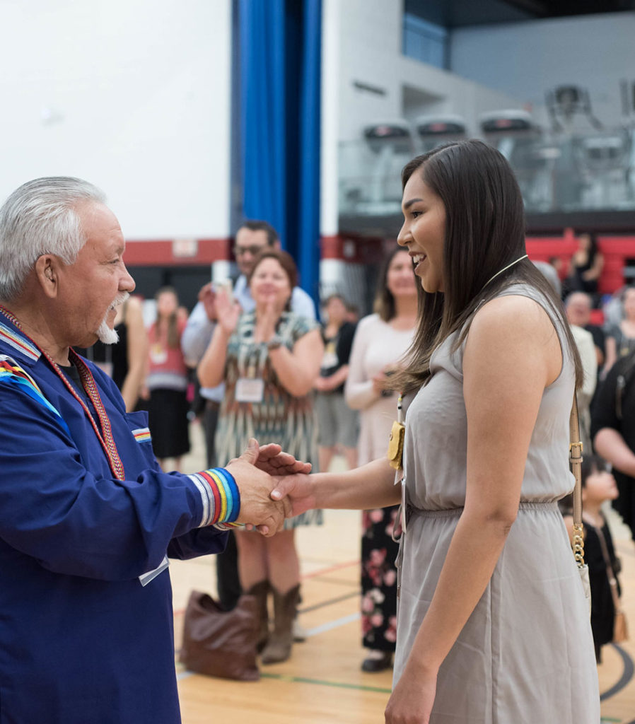 indigenous woman shaking hands with elder at graduation event